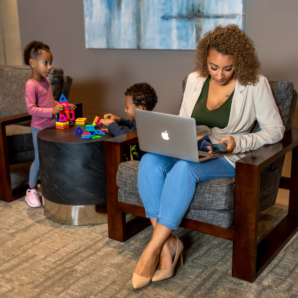 Woman working remotely with her kids playing nearby